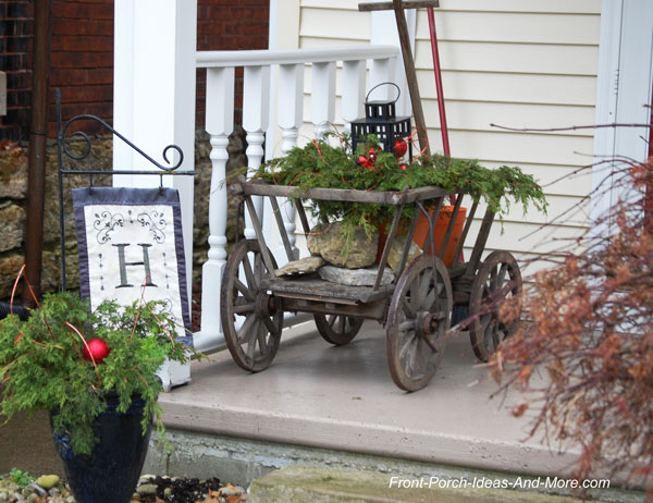 old wagon with evergreens on porch for Christmas