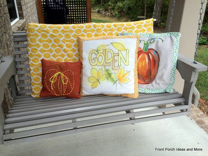 front porch swing with autumn pillows