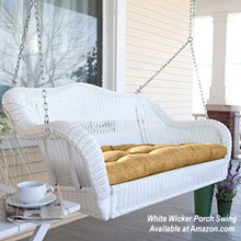 beautiful white wicker porch swing on front porch