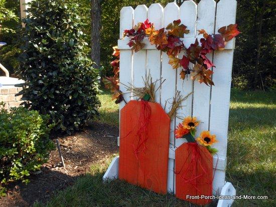 wooden autumn pumpkin fence decoration in yard