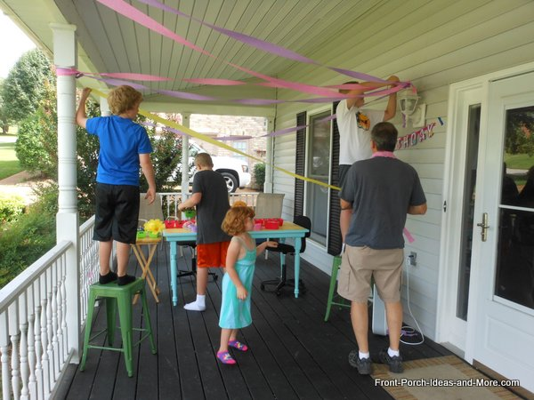 family decorating front porch for birthday celebration