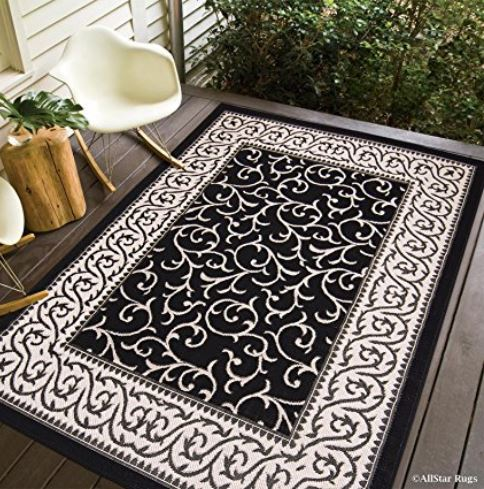 classy black and white scroll patterned indoor outdoor rug with iron chair on front porch