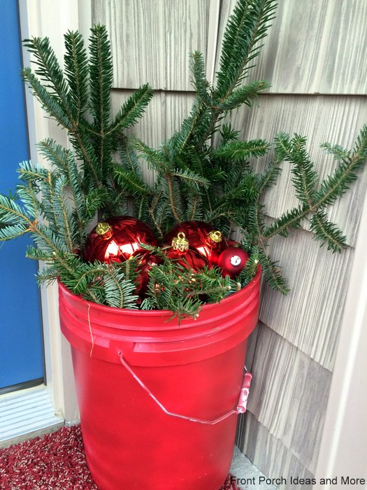 Paint bucket painted red and filled with greenery and ornaments makes for a nice display in the corner of the porch