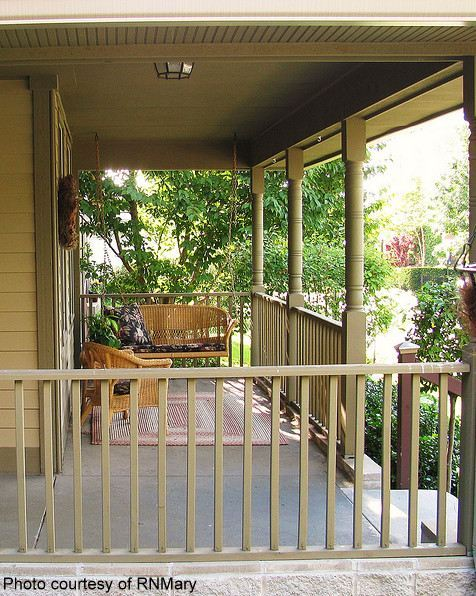 pretty country porch with porch swing, rug and chair