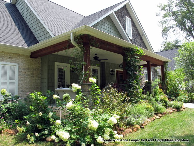 Craftsman porch surrounded by country flower garden