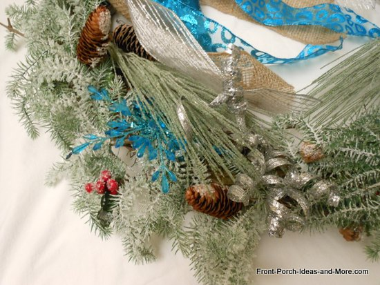 close-up of aqua snowflakes and silver squiggly ornaments tucked beneath evergreen picks
