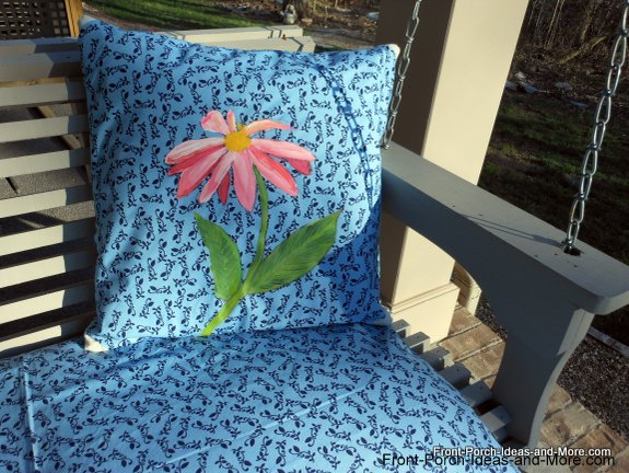 Our pink daisy pillow on the porch swing