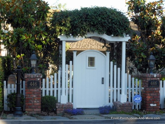 picket fence gate with arbor in front of home