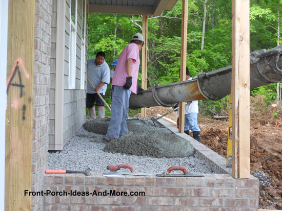 pouring concrete over stone foundation on front porch