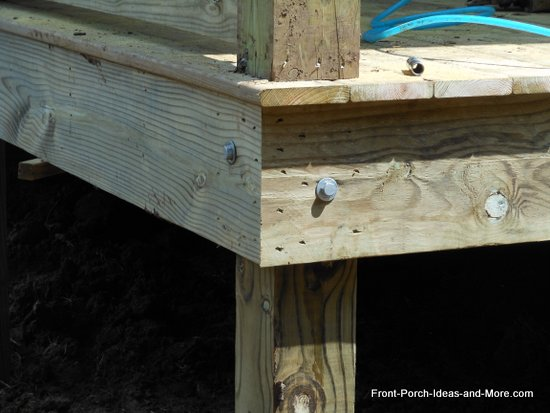 rim joists are secured to the porch posts with lag screws