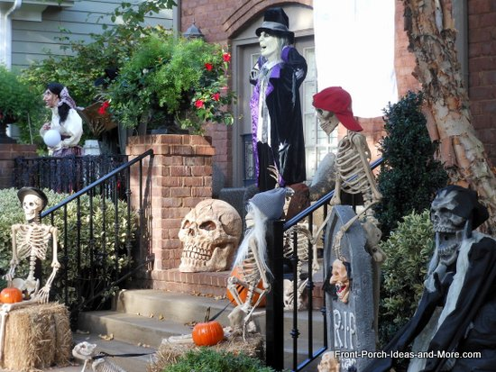 scary halloween decorations - skeletons sitting on bales of hay and wearing baseball caps