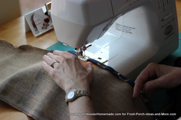 Mary sewing the side hems on the burlap