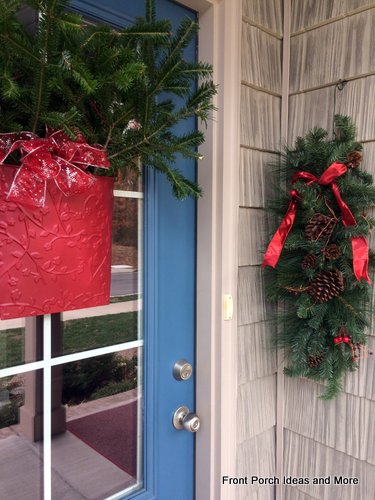 Fresh greenery and red bows dress up our front door