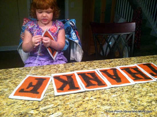 thankful banner - granddaughter pulling the twine through the letters to connect them