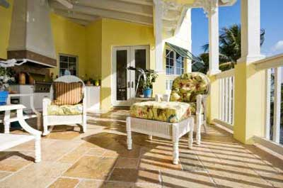 tiled porch floor with wicker furniture and yellow house
