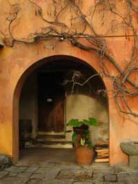 Tuscany porch with arched entryway and terra cotta pots
