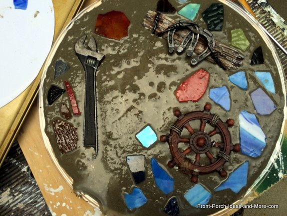 After the largest mementos pieces were placed in the wet concrete mix, we started adding the mosaic stained glass pieces around them.