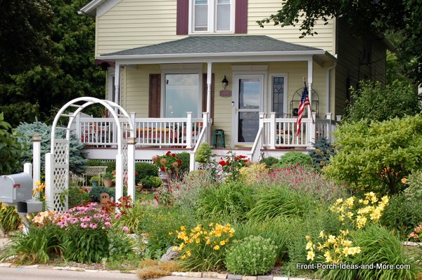 Pretty yellow home with flower garden in front of porch