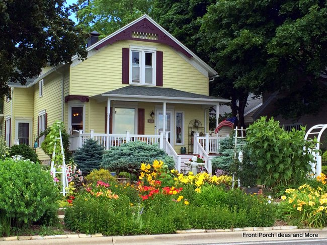 beautiful yellow house with porch and flowers